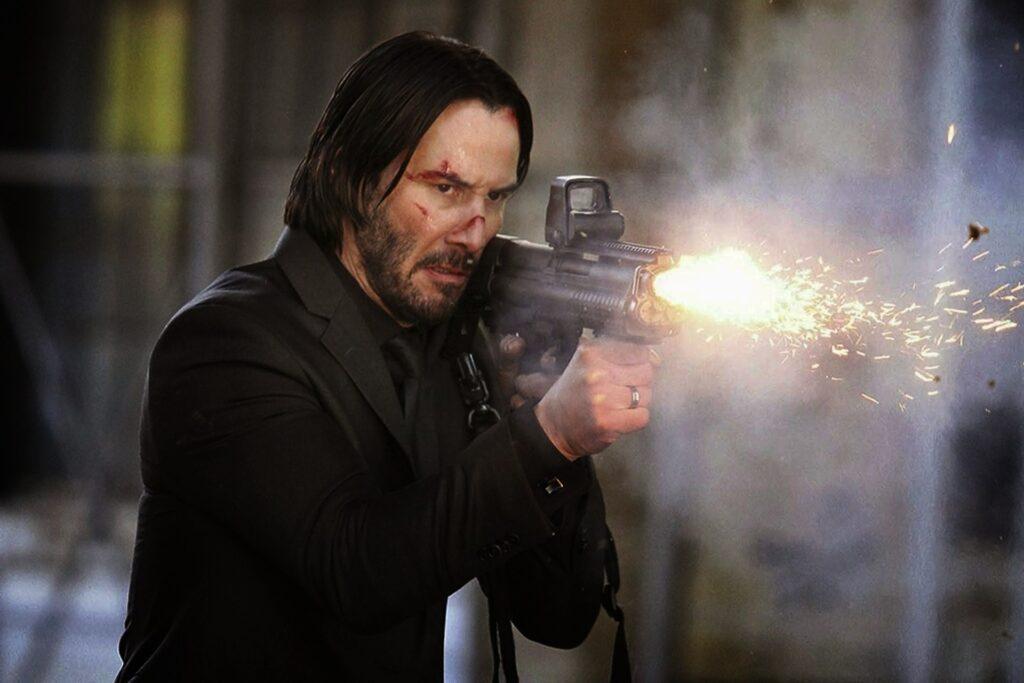 Keanu Reeves como Jonh Wick disparando una arma de fuego.